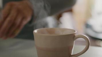 close-up de uma xícara de chá, mãos de um jovem asiático segurando a xícara de chá, mergulhe o saquinho de chá na água e pega a xícara video
