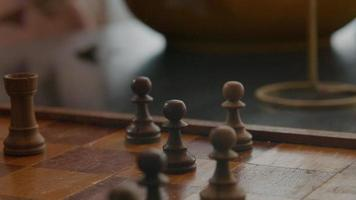 Close-up de parte del tablero de ajedrez y piezas de ajedrez en la mesa, la mano del joven negro mueve piezas video