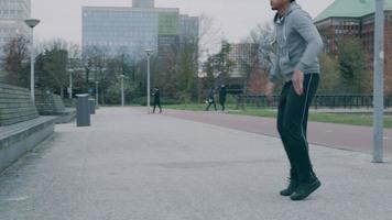 jovem asiático no parque, fazendo exercícios físicos, pulando e movendo os braços no ar