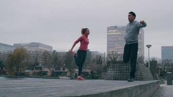 Joven asiático y joven negra en el parque frente al mar, haciendo ejercicio físico, balanceándose sobre una pierna, la otra pierna doblada