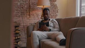 homem maduro sentado no sofá assistindo ao tablet, recostado no apoio de braço, perna esticada no sofá, outra mão tocando a cabeça, parte superior do corpo se movendo ligeiramente