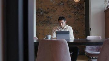 Asian young man sits at table with laptop, having conversation by video-call