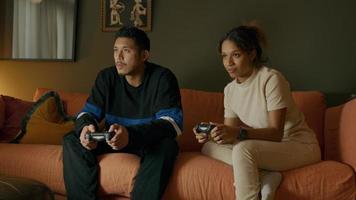 jovem asiático e jovem negra sentados no sofá, ambos jogando no controle remoto, brincando video