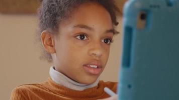 close-up da menina, tablet na frente dela, movendo-se com uma caneta stylus, olhos focados no tablet, toca seu rosto brevemente e fala