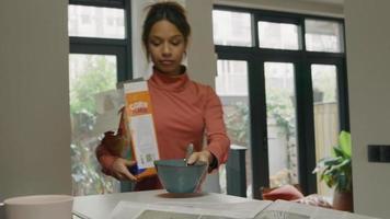 svart ung kvinna går med cornflakes och en skål, lägger dem på bänken och sätter sig ner video