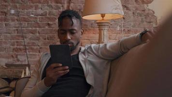 Mature man sits on sofa, watching and holding tablet with one hand in front of him. Other hand on backrest, having a look on his smartwatch, talks shortly, looks at smartwatch again