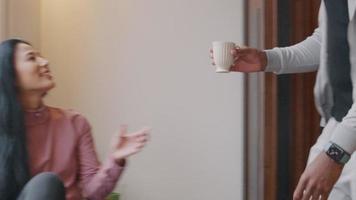 homem maduro dá xícara para mulher madura, que pega a xícara com as duas mãos, sorri. pega o telefone celular, olha, enquanto segura o copo com a outra mão