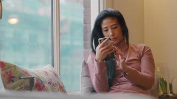 Mujer madura sentada en el alféizar de la ventana, sosteniendo el teléfono celular frente a ella, escribiendo y desplazándose en él