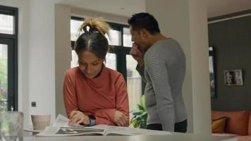 schwarze junge Frau liest und blättert Seite, während asiatischer Mann hinter ihr geht