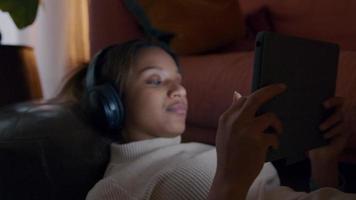 primer plano, de, negro, mujer joven, acostado, en, alfombra, auriculares, en, cabeza, dispositivo de sujeción, mirar, ella video
