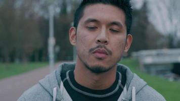 close-up de um jovem asiático, do lado de fora, olhando para a direita - câmera, olhando para a câmera, colocando máscara facial video