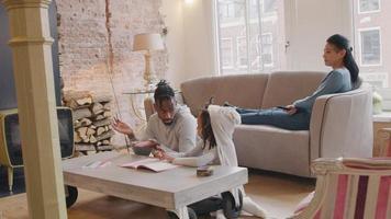 man och flicka sitter på golvet vid bordet. bok och kritor framför dem. de pratar, man gester, tittar på flickan och flickan tittar på mannen. båda börjar rita i arbetsboken. med pennor. kvinna sitter med utsträckta ben på soffan, tittar på tv, var ... video