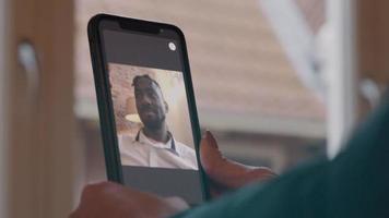close-up de telefone celular, segurado por duas mãos de mulher. videochamada com o homem.