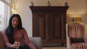 mogen kvinna sitter på soffan, pratar levande, skrattar, håller koppen i handen video