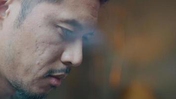 close-up de jovem asiático, focado, cabeça baixa