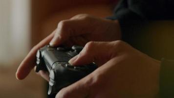 Cerca del joven asiático, mirando enfocado, manos jugando en la consola de juegos