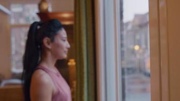 close-up de mulher asiática, olhando pela janela, coloca máscara facial, ajusta e sai video