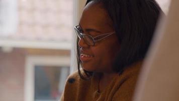 Frau schaut mit gesenkten Augen zu, lächelt, redet video