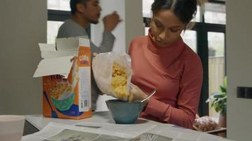 Joven negra pone copos de maíz en un tazón, mientras que el hombre pasa detrás de ella video