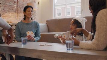 dos mujeres, un hombre y una niña sentados alrededor de la mesa, jugando a las cartas video
