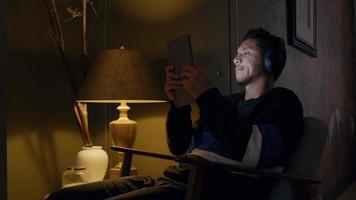 asiatischer junger Mann sitzt im Sessel, Kopfhörer an, tippt auf Tablette, lehnt sich zurück und hält Tablette näher an Kopf
