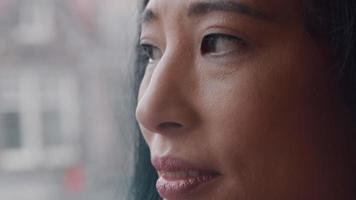 close-up de uma mulher madura, olhando contemplativamente pela janela, bebendo, o copo na mão video