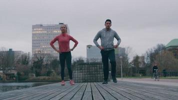 jovem asiático e uma jovem negra no parque à beira-mar fazendo exercícios, praticando ajoelhados, alternando as pernas para a frente