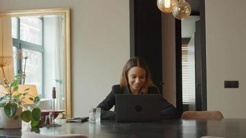 Joven empresaria negra sentada en la mesa con videollamada