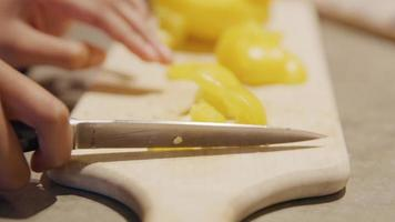 Cerca de las manos de la niña cortando pimentón y moviendo las piezas cortadas con un cuchillo en la tabla de cortar video