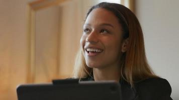zwarte jonge zakenvrouw zittend aan tafel met een video-oproep, spontaan praten video