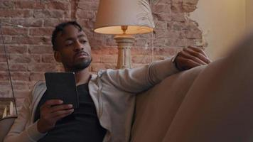 homem maduro sentado no sofá, com as costas apoiadas no braço, segurando o tablet, olhando para o smartwatch, olhando para o tablet e sorrindo video