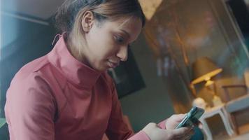 Joven negra en la sala de estar, sosteniendo el teléfono móvil frente a ella, mientras escribe en él