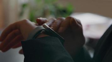dito di giovane donna nera tocca smartwatch primo piano del volto di donna