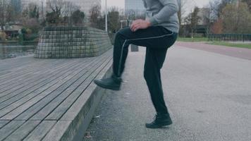 jovem asiático no parque, fazendo exercícios físicos, pulando, alternando os pés tocando o banco à sua frente