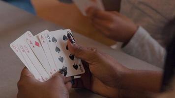 feche as mãos de uma mulher se movendo, jogando cartas, rosto e cabelo parcialmente mostrados, garota no fundo