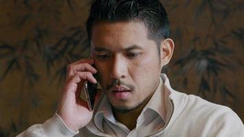 jovem asiático ligando com o celular, focado video