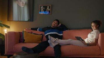 svart ung kvinna och asiatisk ung man sitter på soffan och tittar på tv video
