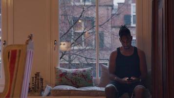 svart man sitter på fönsterbrädan och tittar på mobiltelefonen.