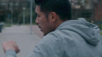 jovem asiático no parque, fazendo exercícios físicos, movimentos de boxe com os braços e punhos na frente dele