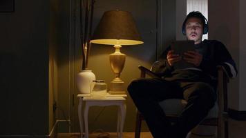 jovem asiático sentado na poltrona, fone de ouvido, ocupado assistindo e digitando no tablet