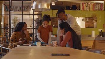 meisje staat voor tafel kijken en scrollen op kinderen tablet. twee vrouwen die rond de tafel zitten en een man die allemaal naar de tablet kijkt. vrouw aan de linkerkant - camera - praat met meisje, wijst naar tablet, meisjesgesprekken, rollen, tikken en gebaren. video