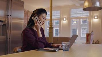mulher asiática madura se senta à mesa da cozinha, enquanto digita no laptop, com o celular no ouvido, falando