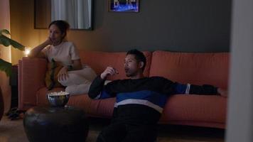 jovem negra e jovem asiático assistindo televisão, comendo pipoca, homem falando video