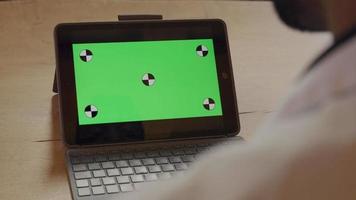 bärbar dator med grön skärm på bordet, mogen man pratar och gör en gest framför bärbar dator video