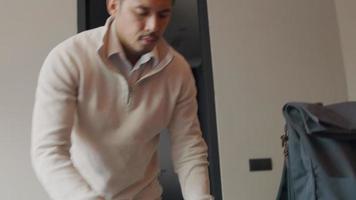 asiatischer junger Mann betritt das Zimmer, steckt Laptop, Stift und Notizbuch in den Rucksack, schließt ihn und geht video