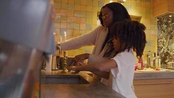Frau und Mädchen vor dem Waschbecken schütteln ihre nassen Hände über dem Waschbecken, Frau dreht den Wasserhahn ab, nimmt Papiertuch, Mädchen nimmt ein Stück Papiertuch
