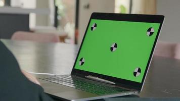 tela verde na tela do laptop, mão esquerda de uma jovem negra movendo-se na frente do teclado-mousepad video