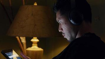close-up de jovem, sentado, focado na tela do tablet, fone de ouvido video