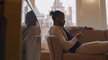 homem maduro assiste ao tablet sentado no sofá, com as costas apoiadas no braço video