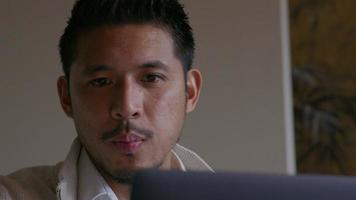Asian young man talking, watching laptop screen